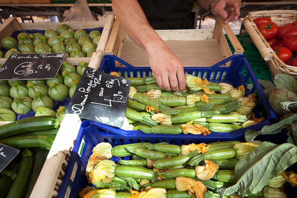 Chef Giorgio Grilenzoni of 'Chat Noir, Chat Blanc' restaurant buys locally-grown courgettes at the Cours Saleya market, Nice, France, 10 April 2012