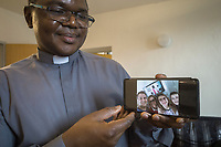 """Switzerland. Canton Ticino. Grancia. Reverend Father Gerald Chukwudi Ani did celebrate the Sunday mass at home and transmit it live on YouTube. Don Gerald Chukwudi Ani, originally from Nigeria, is a catholic priest from the Diocese of Lugano. On his Samsung smartphone, after the end of mass, he has received a picture taken by the Pozzoli family ( Left to right: Luca, Valeria, Martina and Andrea). The family took a selfie at home with the priest on television. Due to the spread of the coronavirus , the Federal Council has categorised the situation in the country as """"extraordinary"""". It has issued a recommendation to all citizens to stay at home, especially the sick and the elderly. From March 16 the government ramped up its response to the widening pandemic, ordering the closure of bars, restaurants, sports facilities and cultural spaces. Celebrating masses is prohibit in order to avoid people meeting together. A selfie is a self-portrait digital photograph, typically taken with smartphone held in the hand. YouTube is an American online video-sharing platform. Grancia is a municipality in the district of Lugano in the canton of Ticino in Switzerland. 29.03.20 © 2020 Didier Ruef"""