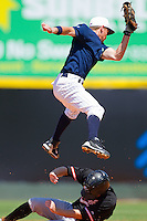 Second baseman Rob Hudson #5 of the Charlotte Knights jumps high for a throw as Blake Davis #1 of the Norfolk Tides slides underneath at Knights Stadium July 5, 2010, in Fort Mill, South Carolina.  Photo by Brian Westerholt / Four Seam Images