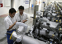 Two Chinese General Motors employees checks inventory on engines about to be shipped to Canada at the Shanghai General Motors plant in Shanghai, China. The engines will be assembled on the GM model Equinox, which is a vehicle made of parts from around the world, very few of which are actually made in the USA..