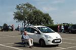 Senior man, oap sunbathing in fold up chair, car park Penarth Wales UK
