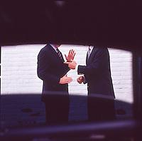Men in suits arguing, seen through limousine window