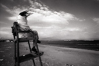 Woman sitting in lifeguard chair on windy day<br />
