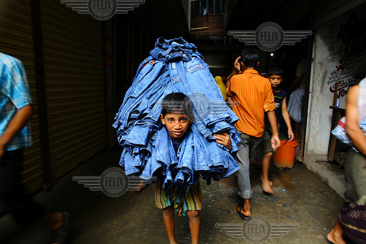 A boy carries a load of newly made denim jeans through the streets of Keranigonj.