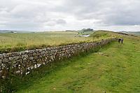 Northumberland,  England, UK.  Hadrian's Wall (Pennine Way) Footpath heading toward Peel Crags in the background.