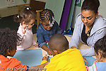 Preschool classroom .female volunteer (parent) working in classroom with children horizontal