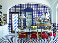 The checked pattern of blue and white ceramic tiles on the walls and floor of this kitchen-diner creates a bright and cheerful room