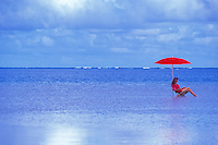A woman sits under a red umbrella reading a book surrounded by the blue ocean.