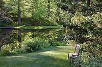 Chairs by pond in woodland garden with small lawn, environmentally-responsible, native plant sustainable garden, Mt Cuba Center Delaware