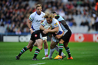 Ross Batty of Bath Rugby is tackled by George Lowe and Danny Care of Harlequins