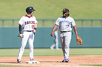 Surprise Saguaros third baseman Vladimir Guerrero Jr. (27), of the Toronto Blue Jays organization, shares a laugh with Dom Miroglio (55) during an Arizona Fall League game against the Salt River Rafters at Salt River Fields at Talking Stick on October 23, 2018 in Scottsdale, Arizona. Salt River defeated Surprise 7-5 . (Zachary Lucy/Four Seam Images)