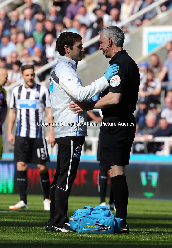 Pictured: Referee Chris Foy (R) is checked over by the Newcastle United physio after getting knocked over by a deflection from a Jonjo Shelvey shot of Swansea. Saturday 19 April 2014<br /> Re: Barclay's Premier League, Newcastle United v Swansea City FC at St James Park, Newcastle, UK.