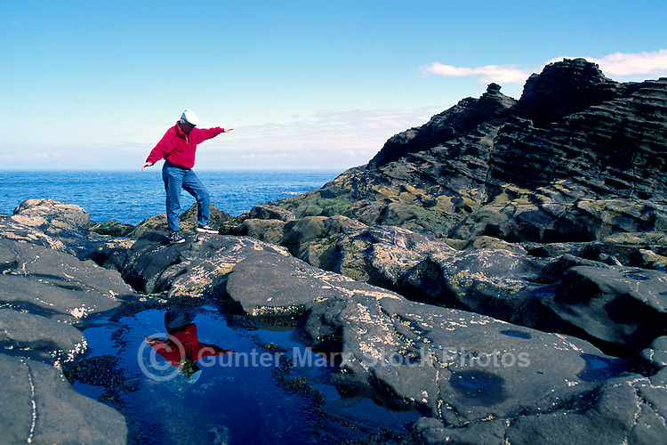 Haida Gwaii (Queen Charlotte Islands), BC, Northern British Columbia, Canada - Hiker hiking on Rocky Shoreline at North Beach along McIntyre Bay,  Naikoon Provincial Park, Graham Island, Summer