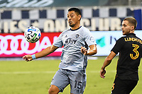 KANSAS CITY, UNITED STATES - AUGUST 25: Roger Espinoza #15 of Sporting Kansas City controls the ball watched by Adam Lundkvist #3 of Houston Dynamo  a game between Houston Dynamo and Sporting Kansas City at Children's Mercy Park on August 25, 2020 in Kansas City, Kansas.