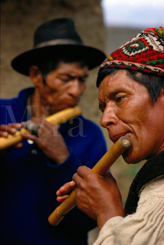 Quechua Indians playing flute at village festival in Ayata in the Andes in Bolivia..