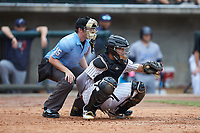 Birmingham Barons catcher Alfredo Gonzalez (34) frames a pitch as home plate umpire Austin Jones looks on during the game against the Pensacola Blue Wahoos at Regions Field on July 7, 2019 in Birmingham, Alabama. The Barons defeated the Blue Wahoos 6-5 in 10 innings. (Brian Westerholt/Four Seam Images)