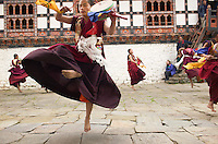 Monks dancing to ward off evil spirits during a festival at a local monastery.