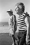 Two sun tanned old age pensioners power walking Bondi beach Sydney Australia.