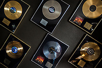 Switzerland. Canton Ticino. Cagiallo. Framed gold and silver records for sales' success by Gotthard band on the wall at Leo Leoni's home. Gotthard is a Swiss hard rock band founded in Lugano by Steve Lee and Leo Leoni. Their last eleven albums have all reached number 1 in the Swiss album charts, making them one of the most successful Swiss acts ever. With 2 million albums sold, they managed to get multi-platinum awards in different parts of the world. Cagiallo is a village and and is part of the Capriasca municipality. 25.03.2019 © 2019 Didier Ruef
