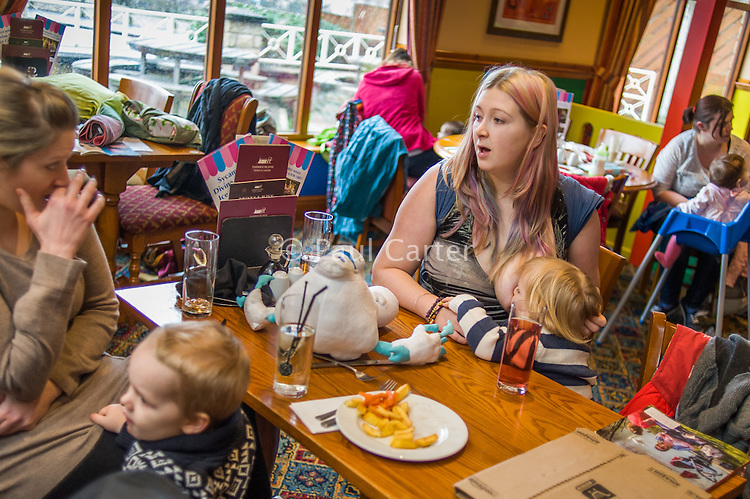 A mother sitting at a table talks to a friend while breastfeeding her two year old daughter in the family restaurant and play area of a pub.<br /> <br /> Lancashire, England, UK<br /> <br /> Date Taken:<br /> 07-01-2015<br /> <br /> © Paul Carter / wdiip.co.uk