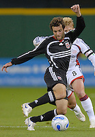 DC United midfielder Ben Olsen (14) dribbles the ball in front of New England midfielder Joe Francino (8). The New England Revolution defeated DC United 2-1, Saturday, October 7, 2006, at RFK Stadium.