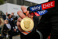The Winners medal - Luton Town players and staff celebrate promotion in front of supporters during an open top bus journey through the streets of Luton displaying the trophy afte gaining promotion to the EFL Championship from League One on 5 May 2019. Photo by David Horn.