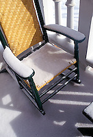 Snow covered rocking chair on porch<br />