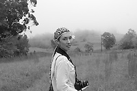 A black and white portrait of a young multiethnic woman with a camera around her neck standing in a field in Pa'auilo Mauka, Big Island of Hawai'i.