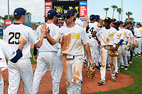 Michigan Wolverines Jonathan Engelmann (2) high fives teammates, including Blake Beers (29), after a game against Army West Point on February 18, 2018 at Tradition Field in St. Lucie, Florida.  Christan Bullock (5) and Ako Thomas (4) follow.  Michigan defeated Army 7-3.  (Mike Janes/Four Seam Images)