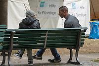 """Die """"Zentrale Aufnahmeeinrichtung des Landes Berlin fuer Asylbewerber"""" (ZAA) des Berliner Landesamt fuer Gesundheit und Soziales (LaGeSo) in der Turmstrasse 21 in Berlin-Moabit. Hier werden alle in Berlin ankommenden Fluechtlinge registriert und bekommen eine Erstversorgung. In dieser Erstaufnahmestelle werden sie auf die vom Land bereitgestellten Unterkuenfte verteilt.<br /> Im Bild: Zwei Fluechtlinge sitzen vor Zelten der Stadtmission. In den Zelten werden bei Bedarf Tee und Kaffee verteilt.<br /> 24.9.2014, Berlin<br /> Copyright: Christian-Ditsch.de<br /> [Inhaltsveraendernde Manipulation des Fotos nur nach ausdruecklicher Genehmigung des Fotografen. Vereinbarungen ueber Abtretung von Persoenlichkeitsrechten/Model Release der abgebildeten Person/Personen liegen nicht vor. NO MODEL RELEASE! Don't publish without copyright Christian-Ditsch.de, Veroeffentlichung nur mit Fotografennennung, sowie gegen Honorar, MwSt. und Beleg. Konto: I N G - D i B a, IBAN DE58500105175400192269, BIC INGDDEFFXXX, Kontakt: post@christian-ditsch.de<br /> Urhebervermerk wird gemaess Paragraph 13 UHG verlangt.]"""
