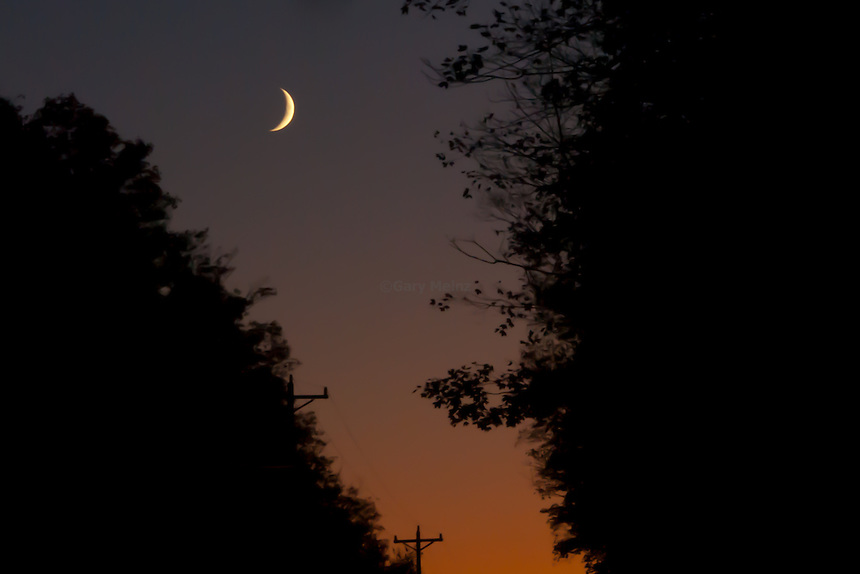 Crescent moon shining over a fading sunset blaze.