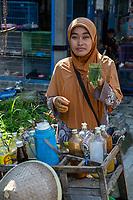 Yogyakarta, Java, Indonesia.  Woman Offering Herbal Drinks as Traditional Medicinal Cures, Bird Market.
