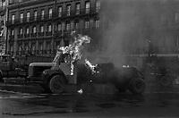 Carrefour boulevard Lazare-Carnot et allées François-Verdier, devant le Monuments aux Combattants. 6 février 1978. Vue d'ensemble d'un camion en feu (vue de profil), flammes, fumée ; en arrière-plan façades début du boulevard Lazare-Carnot. Cliché pris lors d'une manifestation organisée par une trentaine de transporteurs et artisans locaux pour protester contre le chantier de l'autoroute A61 donné à une grosse société du centre de la France. Manifestation patronée par la Confédération Intersyndicale de Défense et d'Union Nationale des Travailleurs Indépendants (CIDUNATI).