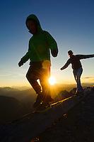 Woman and young boy balancing on log as the sun sets behind them. Harts Pass, Pasayten WIlderness, WA.