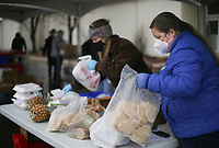 VolunteerAndrea Goucher (right) joins volunteers to pack groceries for clients, Thursday, January 7, 2021 at the Samaritan Community Center in Rogers. Although the building remains closed to clients and guests, Samaritan continued their drive-thru food service, providing hot meals and groceries to anyone in need. The Samaritan cafe and market served 2,235 people with groceries this week between their Springdale and Rogers locations. They distribute food every Tuesday, Wednesday and Thursday at their Rogers location from 10:30 to 12:30 and every Tuesday and Thursday at the same time at their Springdale location. Check out nwaonline.com/210108Daily/ for today's photo gallery. <br /> (NWA Democrat-Gazette/Charlie Kaijo)