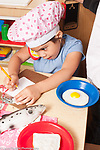 Education Preschool 4 year olds pretend play girl chef writing down food order toy phone at ear