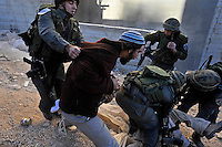 Jewish settlers scuffle with Israeli soldiers after the army evicted the settlers from a disputed building in Hebron. The Israeli high court had rejected the settlers' claim that they legally bought the house from its Palestinian owner. As the house became a symbol of defiance, the few families living there were joined by a mob of some 1,500 radical right-wing youths, who went on a rampage and attacked Palestinians in the mixed West Bank city.