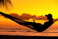 Woman with laptop reclines in a hammock enjoying a Maui sunset at Launiupoko, Maui.