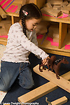 Preschool New York City vertical 4-5 year olds girl in block area pretend play with two plastic horses talking