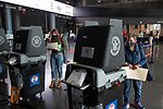 BROOKLYN, NY — OCTOBER 24, 2020:  People wearing face masks scan their ballots inside the Barclay's Center, during the first day of early voting in the U.S. Presidential Election, on October 24, 2020 in Brooklyn, NY.  Photograph by Michael Nagle