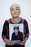 Nurgul Daubai holds a photo of her relative Erkinbek Sybak. He, along with 10 ather people from this family was detained and held in education camp.