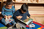 Education preschool 3-4 year olds boy and girl sitting side by side looking at picture books horizontal