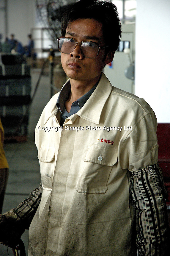 Worker on production line in a privately owned metal works factory, producing parts for major foreign companies including Fuji Xerox, Panasonic, Black & Decker and DeWalt, both for Chinese market and for export (including UK , US and Japan).