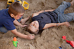 On a school holiday, my sons take turns burying each other in our sandbox.