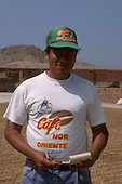 Chiclayo, Peru. Worker, Cafe Nor Oriente, a fair trade partner co-operative supplier of Cafe Direct, coffee drying in the sun.