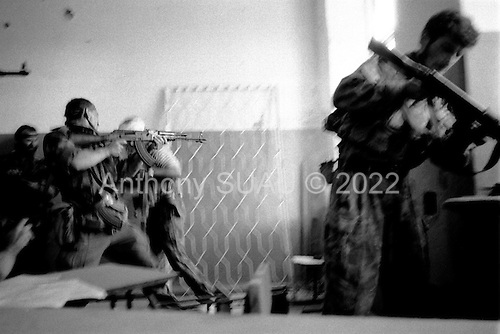Sukhumi, Abkhazia<br /> September 27, 1993<br /> <br /> From a schoolhouse, a Polish professional soldier (left) and an Abkhazian commander (center) run towards the Parliament hoping to place an Abkhazian flag atop. Hundreds of Abkhazian separatists open fire on Georgian forces held up inside. They do not succeed and are repulsed into the schoolhouse. Within hours the Abkhazian separatists control the Parliament building and the city --sending thousands fleeing southward into the mountains as refugees.