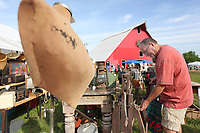 Tim Base looks at an antique laundry roller Friday, June 4, 2021, during the Junk Ranch Spring Show in Prairie Grove. The show continues today featuring vintage, antique, handmade, repurposed, jewelry, boutique, and salvage items with food trucks and live music. Check out nwaonline.com/210605Daily/ and nwadg.com/photos for a photo gallery.<br /> (NWA Democrat-Gazette/David Gottschalk)