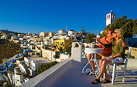Santorini Greece and the beautiful white buildings on the mountain cliffs of main city of Fira and retired couple relaxing on terrace