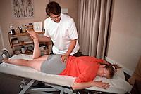 Osteopath performing prone hip articulation on a patient. This image may only be used to portray the subject in a positive manner..©shoutpictures.com..john@shoutpictures.com