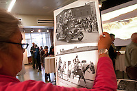 "Angela Buck holds pictures from the Ellensberg Rodeo as a slideshow of images of the Columbia river scroll in front of them at an exhibit called ""Sacred Spaces"" at the Central Washington University Museum of Culture and Environment in Ellensberg, Wash. on February 3, 2011.  (photo credit Karen Ducey)"